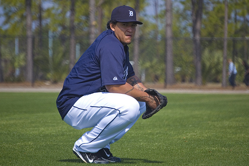 Miguel Cabrera squatting on a practice field